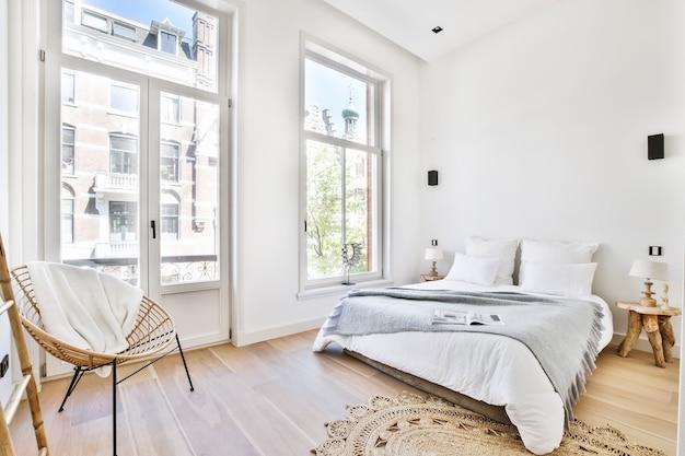 Wygodne łóżko z kocem i poduszkami przy lampkach i fotelu w przestronnej sypialni w nowoczesnym mieszkaniu