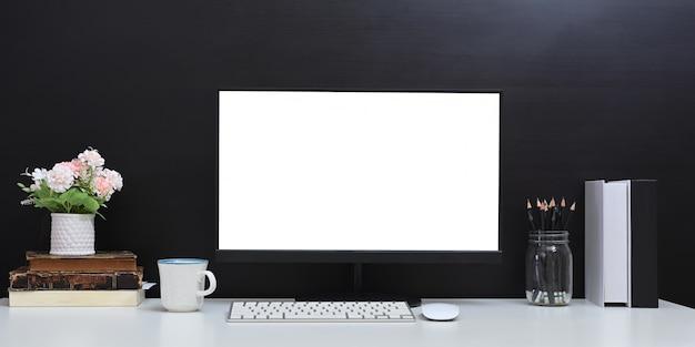Wygodne miejsce do pracy jest otoczone białym, pustym ekranem monitora komputerowego i różnymi urządzeniami