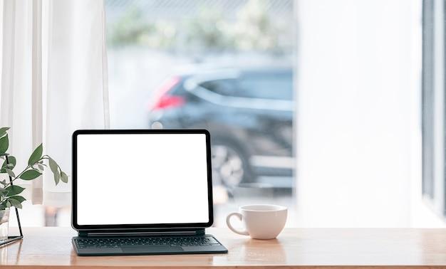 Wygodne miejsce do pracy w domu z tabletem z pustym ekranem i magiczną klawiaturą na drewnianym stole.