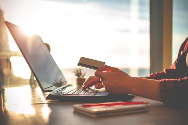 Wygodne miejsce pracy w domowym biurze z laptopem na stole przed oknami o zachodzie słońca dla biznesu online