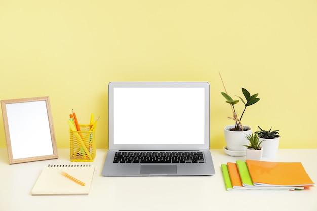 Wygodne miejsce pracy z nowoczesnym laptopem przy kolorowej ścianie