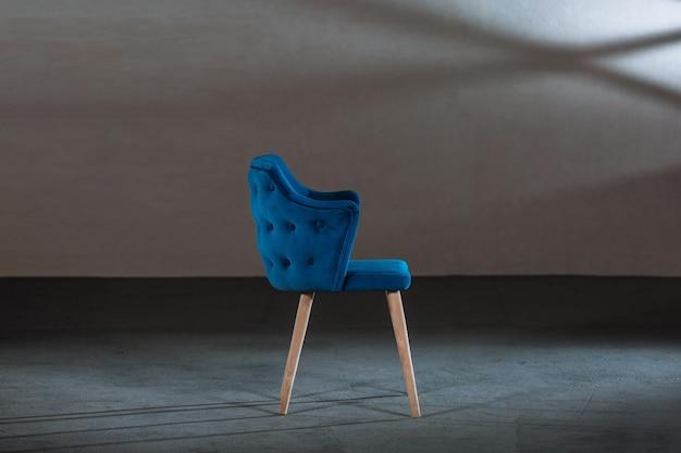 Wygodne niebieskie krzesło skrzydłowe w studio z szarymi ścianami