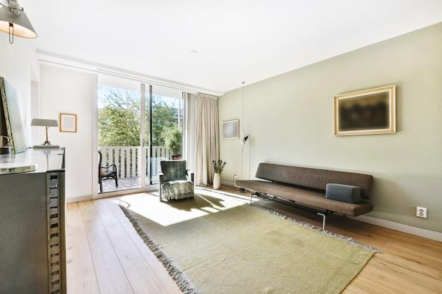 Wygodne siedzenia umieszczone w pobliżu szmatki z tkaniny w przestronnym, jasnym salonie w słoneczny dzień w domu
