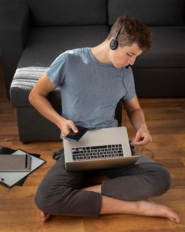 Wygodny człowiek korzystający z laptopa i smartfona w domu w kwarantannie do pracy