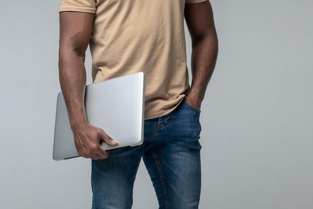 Wygodny laptop. muskularny afroamerykanin w koszulce i dżinsach stoi trzymając laptopa w dłoni, twarz nie jest widoczna