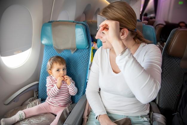 Wygodny lot urocza maluch dziewczyna siedzi w samolocie, matka podnosi maskę do spania i uśmiecha się