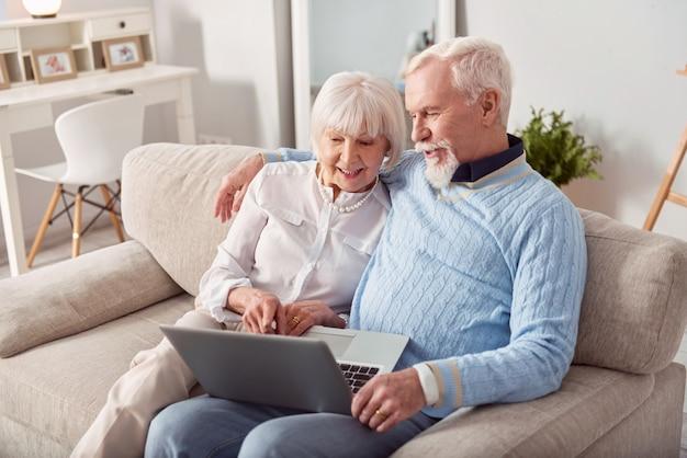 Wygodny zakup. szczęśliwa para starszych siedzi na kanapie w salonie i razem wybiera nowy laptop w sklepie internetowym