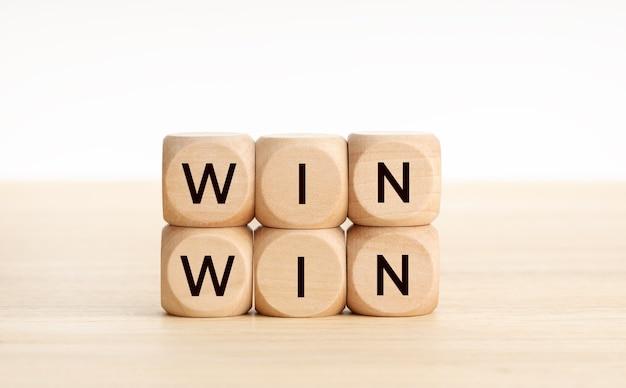 Wygraj wygraj słowo na drewnianych klockach na drewnianym stole.