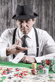 Wygrałem! poważny starszy mężczyzna w koszuli i szelkach rzucający karty na stół pokerowy i patrzący na ciebie