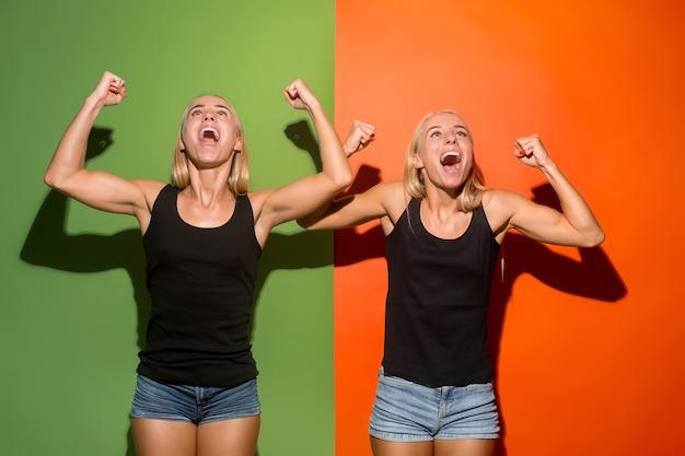 Wygrałem. zwycięski sukces szczęśliwe kobiety świętują zwycięstwo. dynamiczny obraz kaukaskich modelek na tle studia. zwycięstwo, koncepcja radości. koncepcja ludzkich emocji twarzy. modne kolory