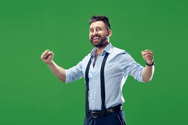 Wygrałem. zwycięski sukces szczęśliwy człowiek świętuje bycie zwycięzcą. dynamiczny obraz kaukaski mężczyzna model na zielono. zwycięstwo, koncepcja radości