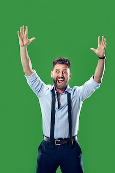 Wygrałem. zwycięski sukces szczęśliwy człowiek świętuje bycie zwycięzcą. dynamiczny obraz kaukaski model mężczyzna na tle zielonego studia