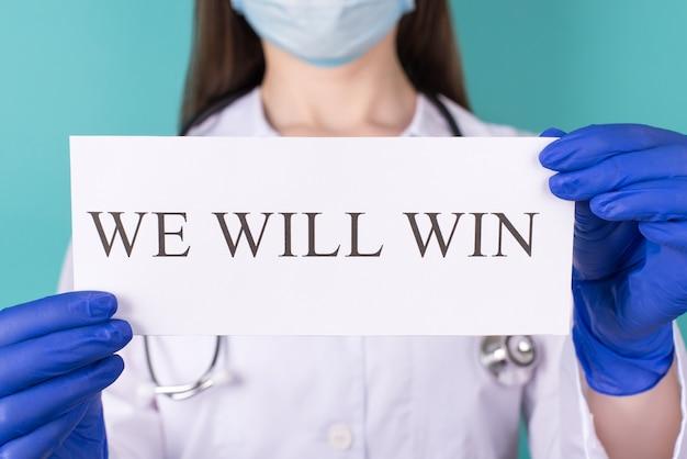 Wygramy koncepcję. zbliżenie przycięte zdjęcie lekarza terapeuty lekarza w białym płaszczu rękawice maska gospodarstwa wygramy papier na białym tle na niebieskim turkusowym tle