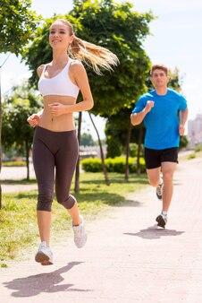 Wygrywam! wesoła młoda kobieta biega wzdłuż drogi z mężczyzną w tle
