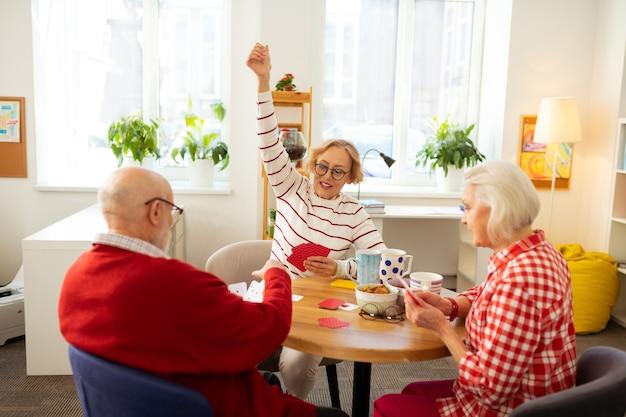 Wygrywam. zachwycona starsza kobieta trzymająca rękę w górze podczas wygrywania gry