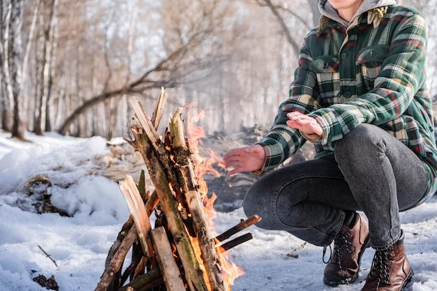 Wygrzewa się w pobliżu ogniska w zaśnieżonym lesie brzozowym. osoba płci żeńskiej w pobliżu ognia w słoneczny zimowy dzień w lesie