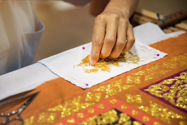 Wyhaftuj złotą koronkę na materiale.