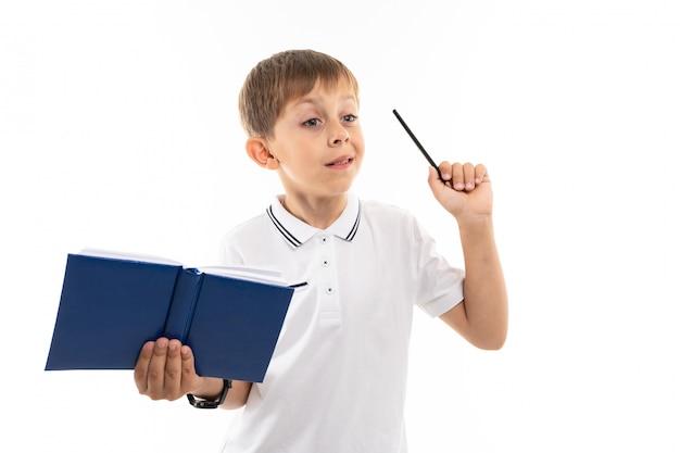Wyjaśnia chłopiec z książką i piórem w rękach na bielu