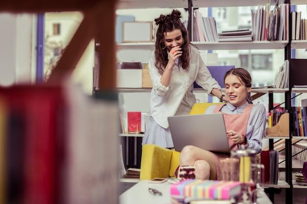 Wyjaśniając jej pracę. roześmiana dziewczyna z kręconymi włosami w białej koszuli obserwująca treść prezentowaną na laptopie swojej przyjaciółki