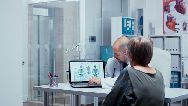 Wyjaśnienie ludzkiego szkieletu starszemu pacjentowi z broszury na laptopie. radiologia i radiografia w nowoczesnym prywatnym szpitalu lub klinice z personelem medycznym chodzącym w tle, pracująca pielęgniarka, służba zdrowia