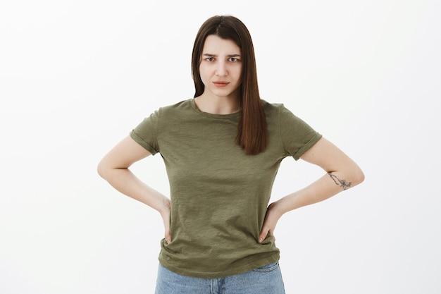 Wyjaśnij się bezgranicznie. portret niezadowolonej i wściekłej młodej apodyktycznej siostry trzymającej się za ręce w pasie, marszczącej brwi i wpatrującej się w osąd, rozczarowanej szarą ścianą