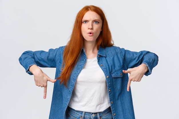 Wyjaśnij to teraz. poważnie wyglądająca szalona i zakłopotana, zmieszana ruda kobieta wskazuje w dół, marszczy brwi i skrzywi się, nie może nie zrozumieć, kto popełnił bałagan, czując złość na białym
