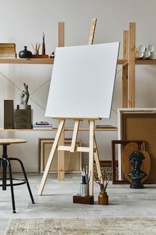 Wyjątkowe wnętrze pracowni artysty z drewnianą sztalugą, regałem, dziełami sztuki, akcesoriami malarskimi, dekoracją i eleganckimi rzeczami osobistymi. nowoczesna pracownia artystyczna. szablon.