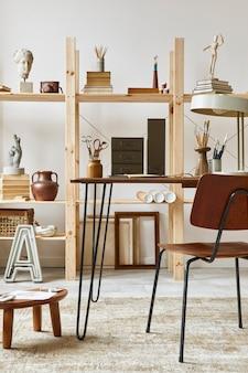 Wyjątkowe wnętrze pracowni artystycznej ze stylowym biurkiem, drewnianą sztalugą, regałem, dziełami sztuki, akcesoriami malarskimi, dekoracją i eleganckimi rzeczami osobistymi. nowoczesna pracownia artystyczna..