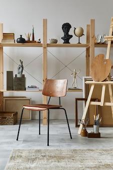 Wyjątkowe wnętrze pracowni artystycznej ze stylowym biurkiem, drewnianą sztalugą, regałem, dziełami sztuki, akcesoriami malarskimi, dekoracjami i eleganckimi rzeczami osobistymi. nowoczesna pracownia artystyczna. szablon.
