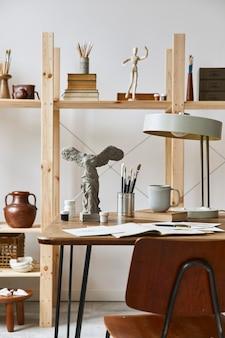 Wyjątkowe wnętrze pracowni artystycznej ze stylowym biurkiem, drewnianą sztalugą, regałem, dziełami sztuki, akcesoriami malarskimi, dekoracjami i eleganckimi rzeczami osobistymi. nowoczesna pracownia artystyczna.