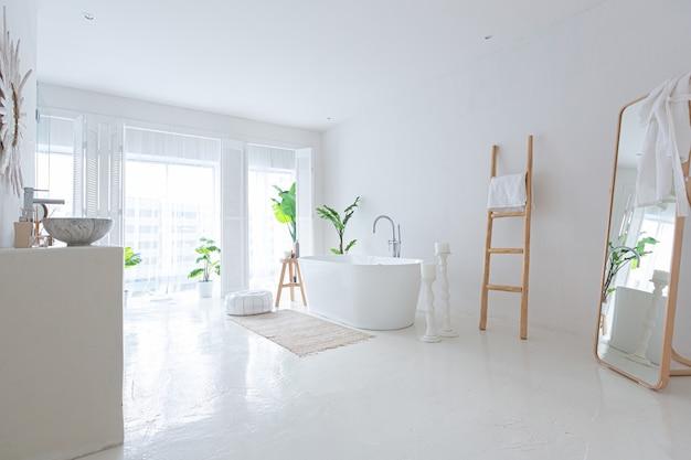 Wyjątkowo białe i bardzo lekkie minimalistyczne stylowe eleganckie wnętrze łazienki z nowoczesną wanną, zielenią i elementami drewnianymi