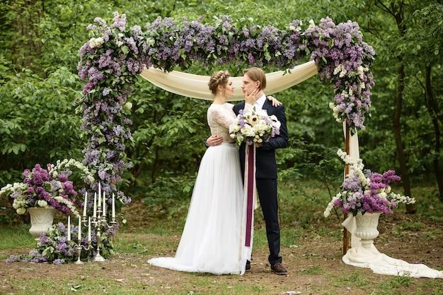 Wyjazdowa ceremonia ślubna w lesie. państwo młodzi stoją w pobliżu łuku z kwiatów bzu