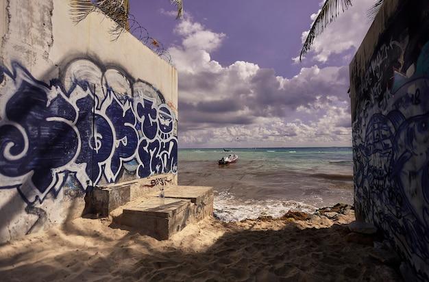 Wyjście z alei z wieloma graffiti, prowadzącej na plażę playa del carmen w meksyku.