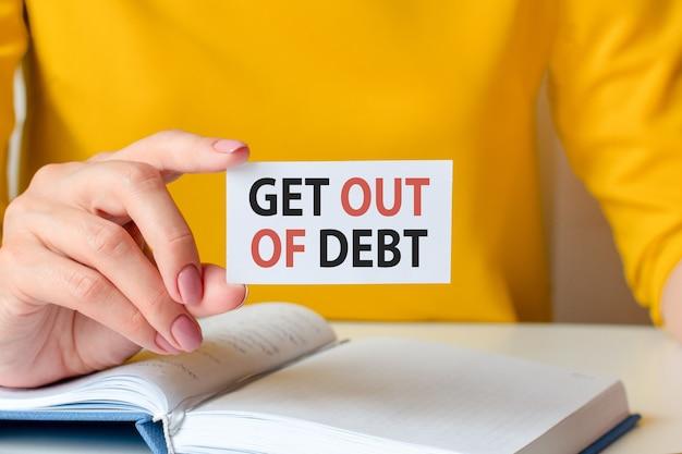 Wyjście z długu jest zapisane na białej wizytówce. kobieca ręka trzyma białą kartkę papieru. koncepcja biznesowa i reklamowa. nieostrość.