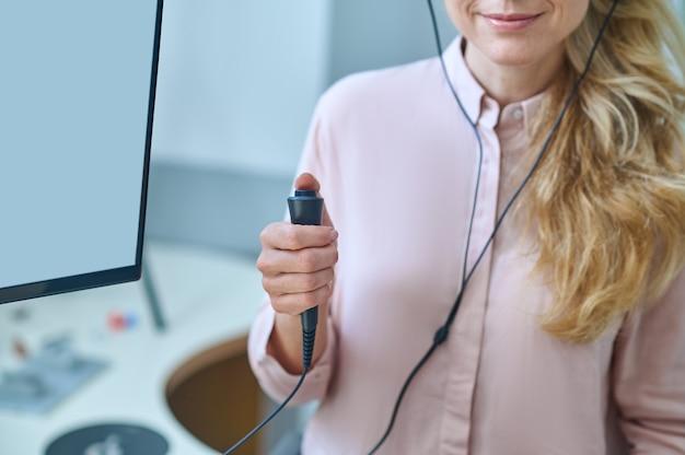 Wykadrowane zdjęcie blondynki, która podczas badania audiometrii naciska przycisk przełącznika odpowiedzi