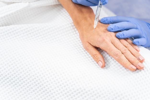 Wykadrowane zdjęcie pacjentki w waflowym szlafroku, w której wstrzykuje się jej wypełniacz skórny