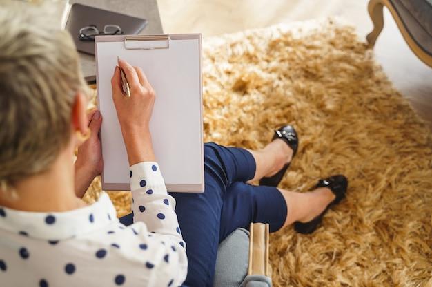 Wykadrowane zdjęcie psychoterapeutki ze schowkiem, która robi notatki podczas sesji terapeutycznej