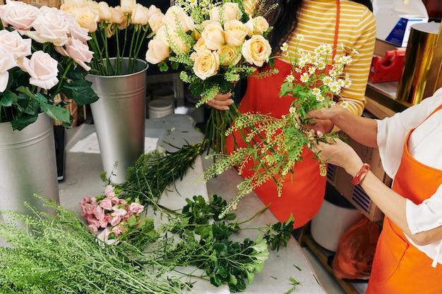 Wykadrowany obraz kwiaciarni w fartuchach robiących piękne bukiety z różami i rumiankami dla klientów