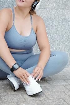 Wykadrowany obraz młodej kobiety w rozmiarze plus odpoczywającej na ziemi po treningu na świeżym powietrzu