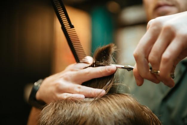 Wykadrowany obraz profesjonalnej stylistki obciętej włosów swojego klienta.