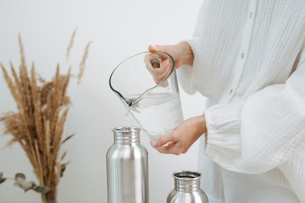Wykadrowany obraz rąk kobiety nalewającej wodę do metalowego termosu z dzbanka. na środku stołu.