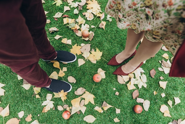 Wykadrowany widok para mężczyzna i kobieta w miłości stojący na zewnątrz z jesiennymi liśćmi na tle. koncepcja stylu życia i relacji