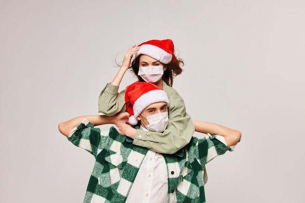 Wykadrowany widok wesołej kobiety w świątecznym kapeluszu i mężczyzny w masce medycznej na jasnej przestrzeni