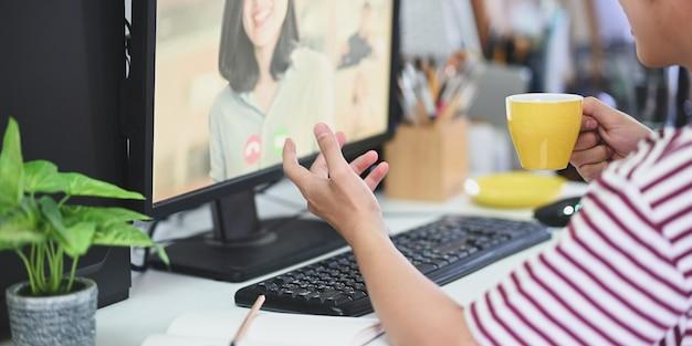 Wykadrowany z kreatywnego mężczyzny trzymającego filiżankę kawy i prowadzenia wideokonferencji.