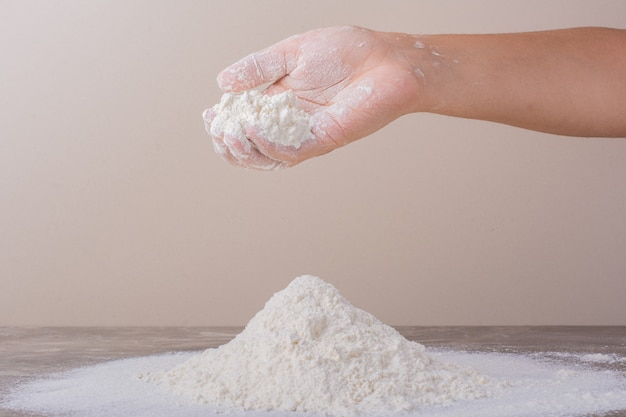 Wykładanie mąki na ziemię do wyrobu ciasta.