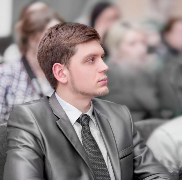 Wykładu słuchają młodzi przedsiębiorcy, siedząc w holu centrum biznesowego