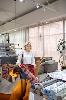 Wykładzina dywanowa. blondyneczka stojąca przy dywanach w salonie meblowym, trzymająca dywanik z pięknym ornamentem, w dobrym nastroju.