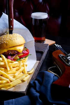 Wykonaj burger wołowy i frytki na stole w restauracji ze szklanką piwa na ciemności. nowoczesna rama obiadowa typu fast food