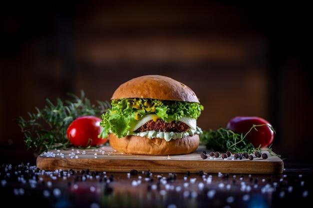 Wykonaj chrupiący burger z kurczaka z serem, sałatą, pomidorem i sosem na drewnianym tle
