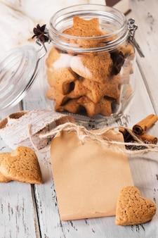 Wykonaj papierową notatkę lub kartkę z życzeniami z imbirowymi ciasteczkami w kształcie serc na drewnianym stole.
